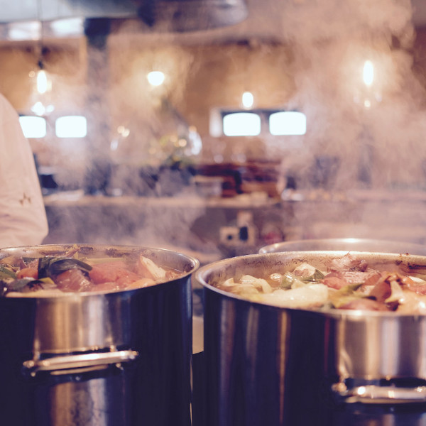 Steaming pots of soup in restaurant kitchen